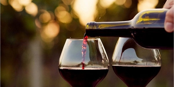 Red Wine being poured into a glass from a bottle.
