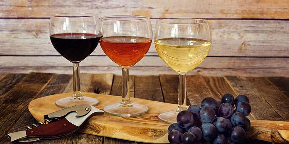 Three Glasses of Colored Wine Placed on the table with Grapes