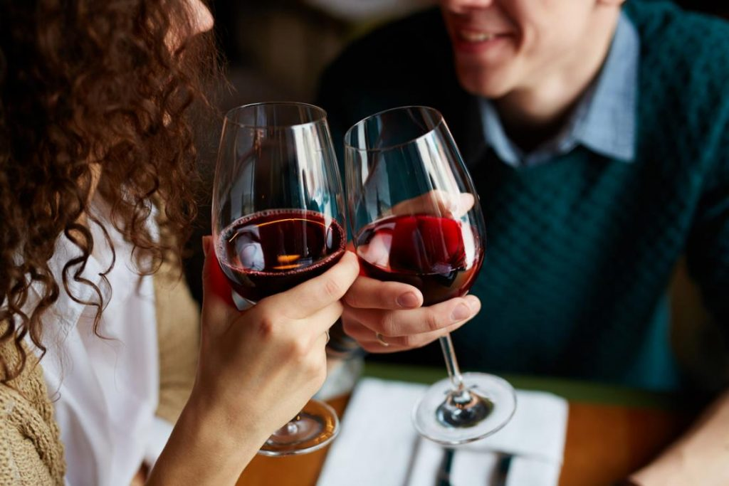 Two people clinking with glasses of red wine