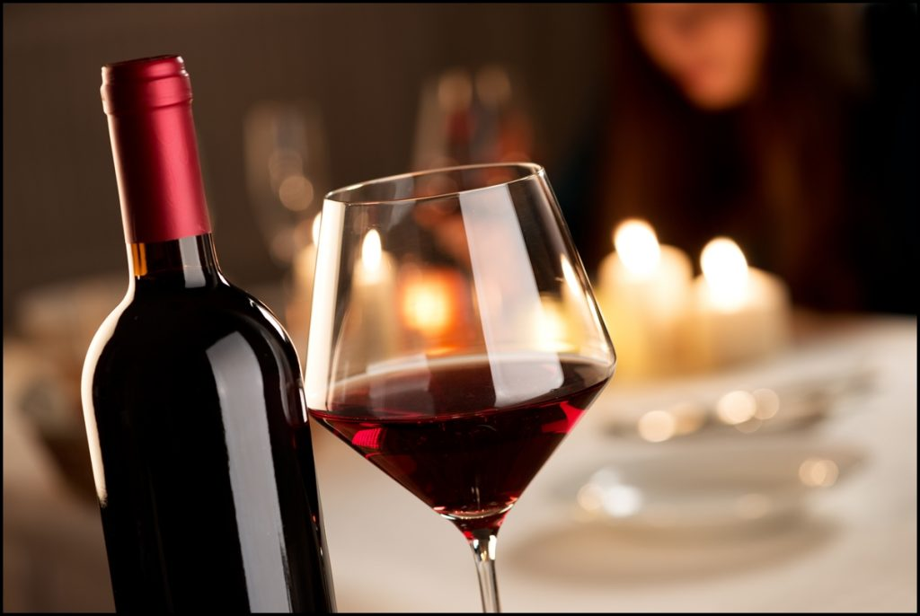Image Shows A Glowing Red Wine Bottle with Glass